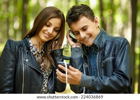 Couple of teenagers friends listening to music on the same pair of headphones - stock photo