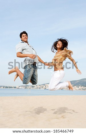 Couple of teenagers having fun, holding hands and jumping up in the air together while visiting a white sand beach on vacation during a sunny day in the summer. Outdoors teenagers lifestyle. - stock photo