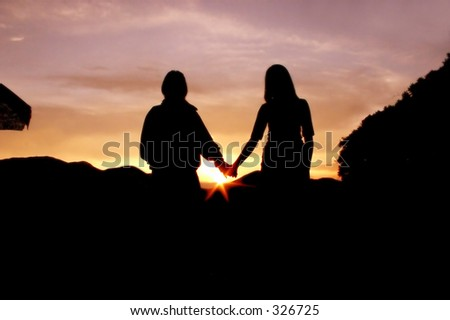 couple of teenagers holding hands in front of a sunset in the andes - stock photo