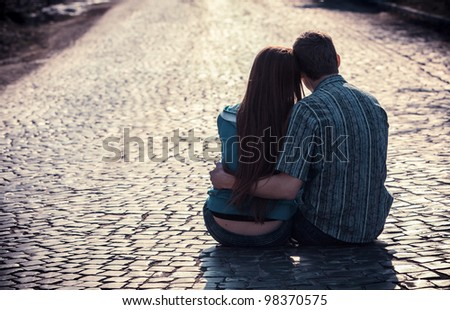 Couple of teenagers sit in street together - stock photo