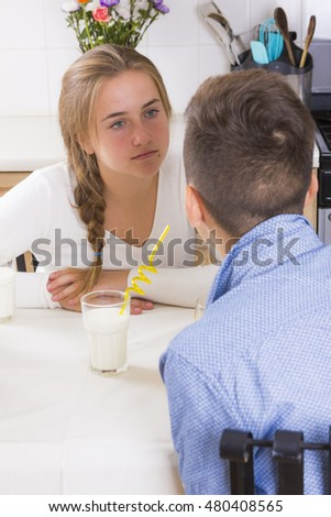 Couple of teens sitting at table and having quarrel