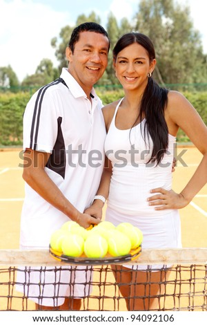 Couple of tennis players at the court holding a racket and balls - stock photo