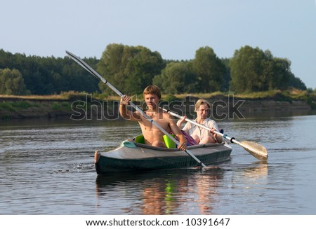 couple of tourist kayaking along the river at summer - stock photo