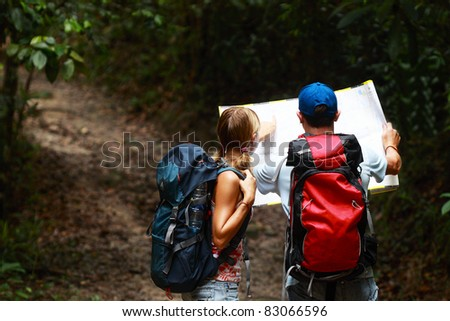 Couple of tourist people looking for a road with map in the dark forest with backpack - stock photo