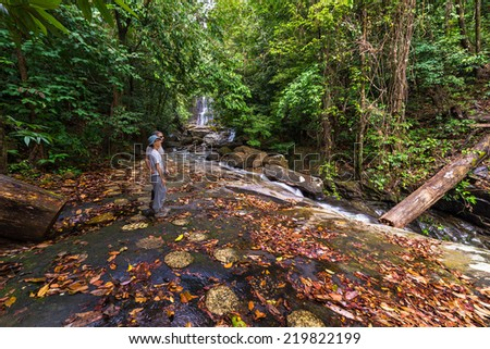 Couple of tourist relaxing at the beautiful waterfall in the rainforest of Kubah National Park, West sarawak, Borneo, Malaysia. - stock photo