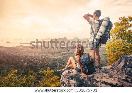 Couple of tourist with backpacks relaxing on top of a mountain and enjoying the view of valley