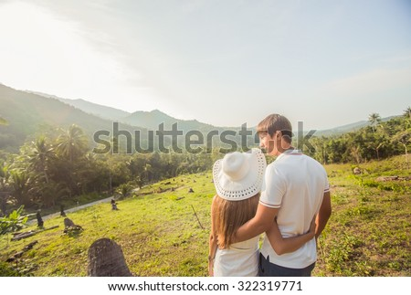 Couple of tourists admiring the view from the mountains, tropical jungles of Thailand, sunset, vacation