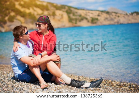 couple of tourists are sittting on the beach