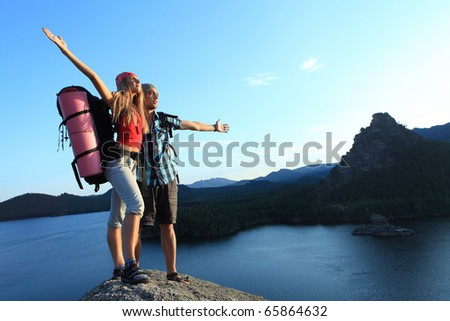 Couple of tourists are standing at the top of a mountain with a feeling of freedom. - stock photo