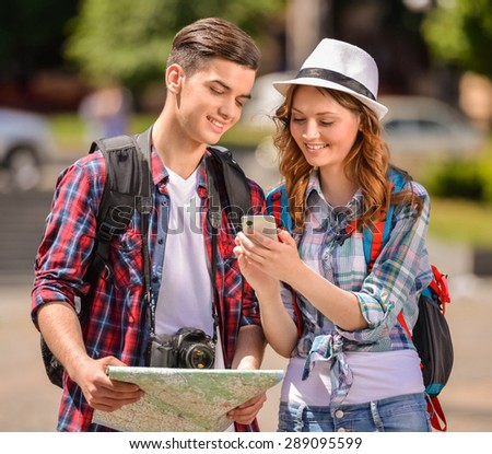 Couple of tourists consulting a city guide and smartphone gps in the street searching locations. - stock photo