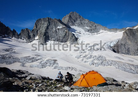 Couple of tourists having a breakfast in high mountains - stock photo