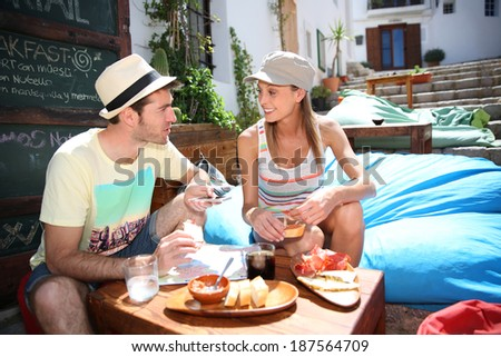 Couple of tourists having finger food in cosy place - stock photo