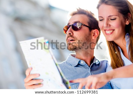 Couple of tourists holding a map and having fun on their holidays - stock photo