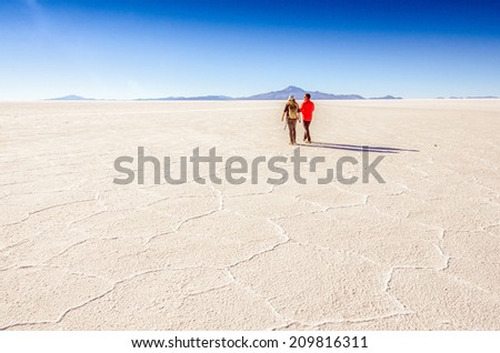 Couple of tourists in Salar de Uyuni, Bolivia  - stock photo