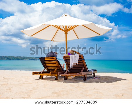Couple of tourists on the beach in Bali - stock photo