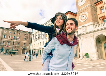 Couple of tourists playing piggyback - Two young cheerful hipsters outdoors in old town central square - happy students having fun in city center - Best friends walking and pointing out retro building - stock photo