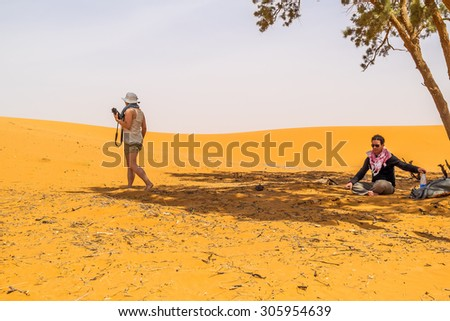 Couple of tourists resting under a tree on sand dunes in Merzouga, Morocco