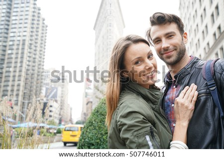 Couple of tourists standing in front of Flatiron building, NYC