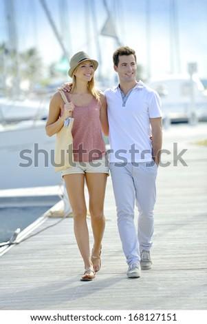 Couple of tourists walking by marina - stock photo
