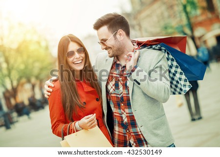 Couple of tourists walking in a city street - stock photo