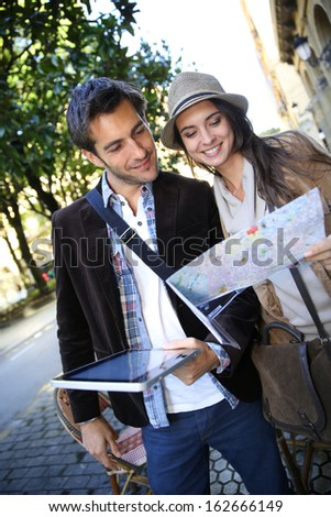 Couple of tourists walking in town with map and tablet - stock photo