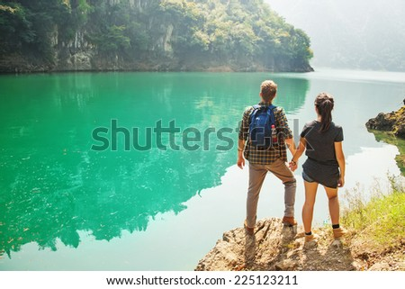 couple of travelers at the gorgeous lake - stock photo