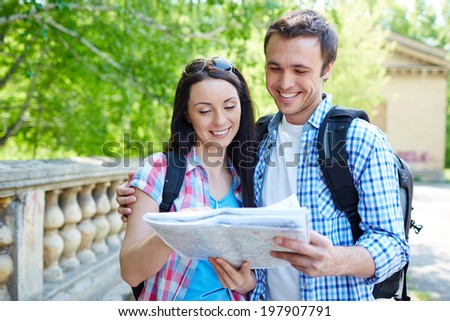 Couple of travelers studying map of ancient town - stock photo