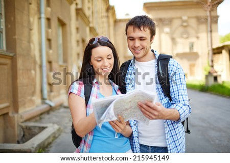 Couple of travelers studying map of ancient town during their journey - stock photo