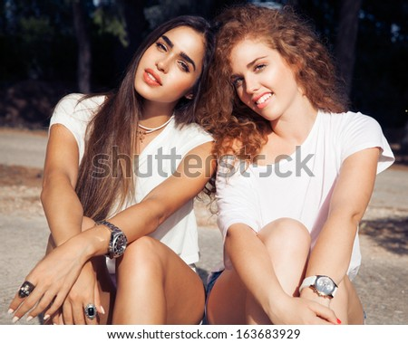 Couple of two beautiful smiling girls in fashion style. Women with long hair. Beautiful best friends in white t-shirts.Urban-street style fashion.Color make up.Fanny girls. outdoors shot, horizontal.  - stock photo