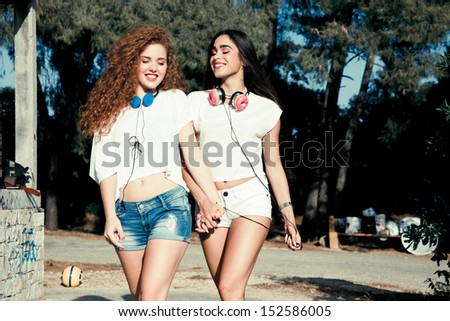 couple of two young girls walking with headphones in a park . horizontal shot. outdoors - stock photo