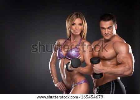 Couple of well trained bodybuilder with dumbbells. Woman and man standing over black background  - stock photo