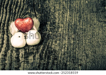 Couple of white pigeons with shiny red heart on old wooden background. Toned. - stock photo
