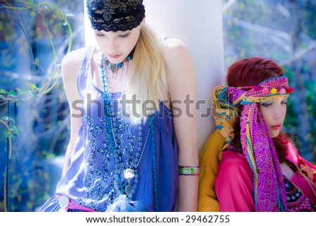couple of women in oriental clothes in garden - stock photo