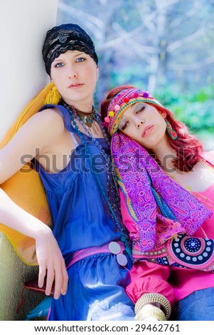 couple of women in oriental clothes resting in garden - stock photo