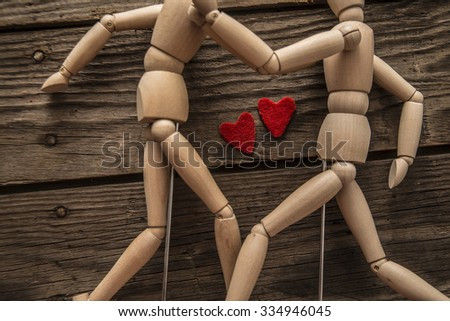 Couple of Wooden dummies hugging. Two Heart between figure. Love.Objects lie on wood old retro vintage aged board texture background  - stock photo