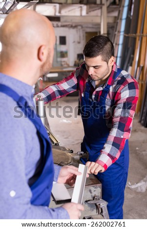 Couple of workers near milling machine at factory inside - stock photo