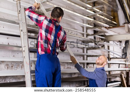 Couple of workmen inspecting window frames at factory inside - stock photo