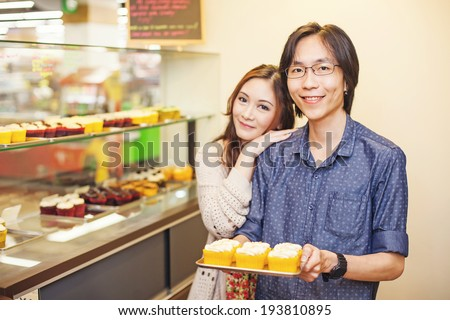 Couple of young and very cute chinese entrepreneurs working together in a family business - stock photo