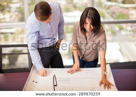 Couple of young architects analyzing a building plan in a meeting room - stock photo