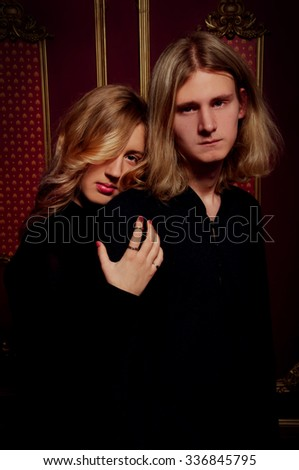 Couple of young blond people dressed in black in a dark gothic room