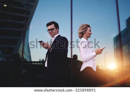 Couple of young businesspeople using cellphones standing against office building with cityscape reflection, two persons having mobile phone conversations while they smiling, messaging on smart-phone - stock photo