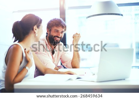 Couple of young designers working at modern office, two coworkers discussing fun project over a laptop, little team of businesspeople smiling and looking together at computer, students at library