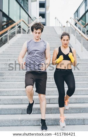 Couple of young handsome caucasian sportive man and woman running downstairs, looking downward - sportive, healthy, fitness concept - stock photo