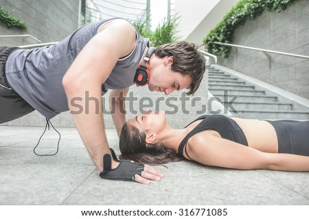Couple of young handsome caucasian sportive man and woman stretching - he is doing push ups looking his girlfriend who is with eyes closed - love, fitness, healthy concept - stock photo