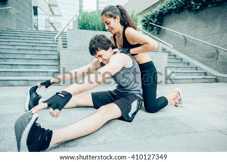 Couple of young handsome caucasian sportive man and woman stretching together - she is helping him stretch his back - both looking downward - sportive, fitness, healthy concept - stock photo
