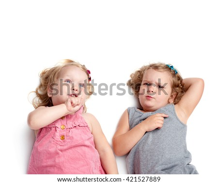 Couple of young little girls sinsters with curly hair in gray and pink dress lying over isolated white background - stock photo