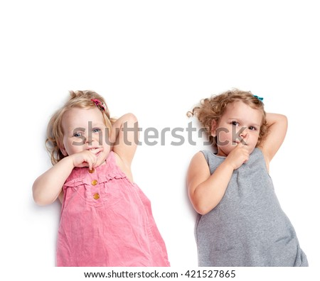 Couple of young little girls sinsters with in gray and pink dress lying and doing shh silence sign over isolated white background - stock photo