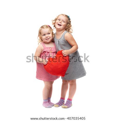 Couple of young little girls sisters with curly hair in gray and pink dress holding red plush heart and standing over isolated white background - stock photo