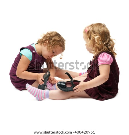 Couple of young little girls sitting over isolated white background - stock photo