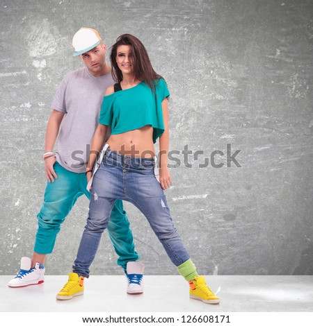 couple of young man and woman  hip-hop dancers, posing at studio. - stock photo